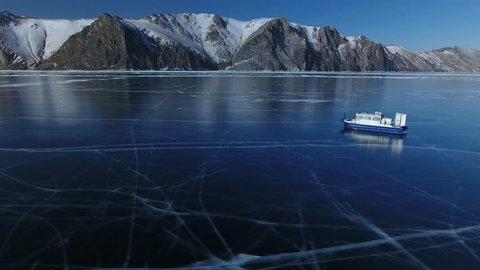 Blue Transparent Ice field Lake Baikal Picturesque cracks. Ship boat an air cushion rides near high mountains. Best Russia North. Tourist attraction. Winter sunny.