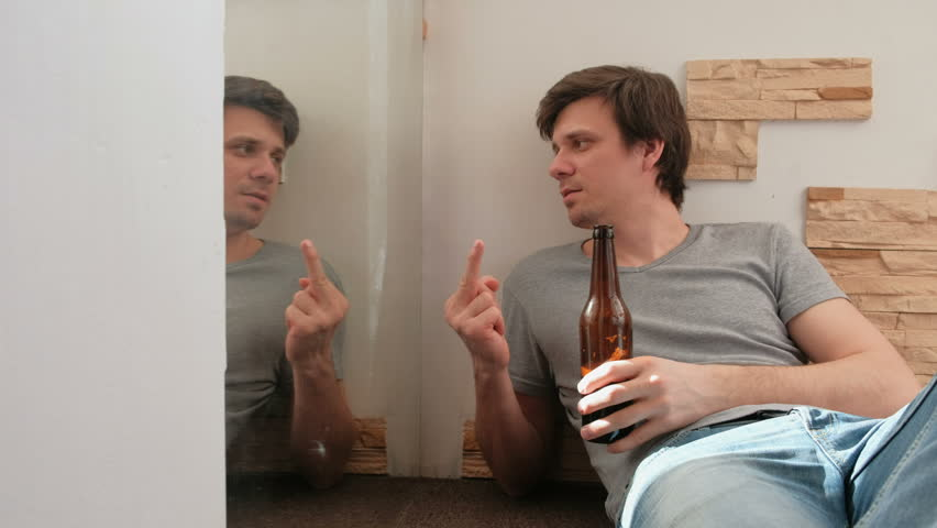 Male bachelor drinking beer and shows fuck you with finger to his reflection in the mirror.