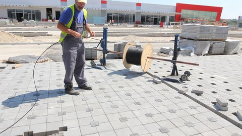 Zrenjanin, Vojvodina, Serbia - August 27, 2015: Cable spool is on the axle until worker unwinds wire at building site.