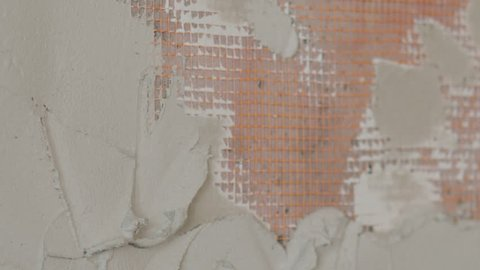 Slow motion pan shot of worker applying plaster on the wall