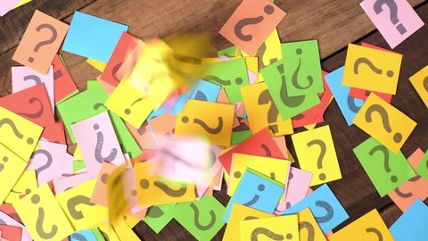 dropping colorful paper note with QUESTION MARK on wooden table. FAQ, questions and problem concept
