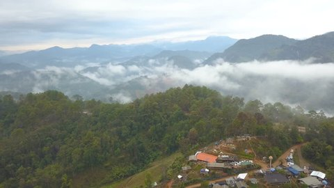 Aerial View. Flying over the high mountains forest with village in beautiful clouds fog, at Doi luang Chiang dao, Chiang mai, Thailand.