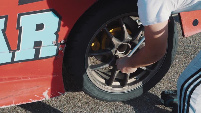Mechanics change the wheel on a racing car