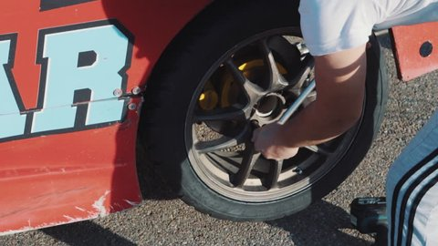 Mechanics change the wheel on a racing car