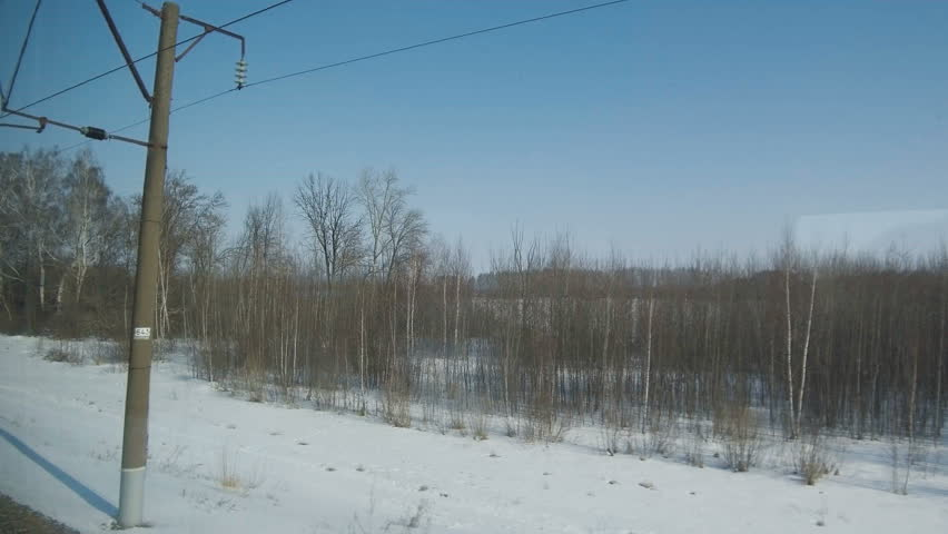 4K Point of view from the window of a passenger train. A typical winter Russian winter landscape moves outside the window.