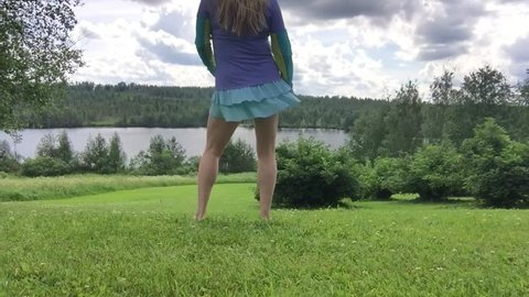 Anonymous barefoot long hair woman dancing hips swinging in green lawn hill, wearing mini skirt sporty legs, beautiful blue lake view, clouds sky, summer trees and bushes bee flying having fun outside
