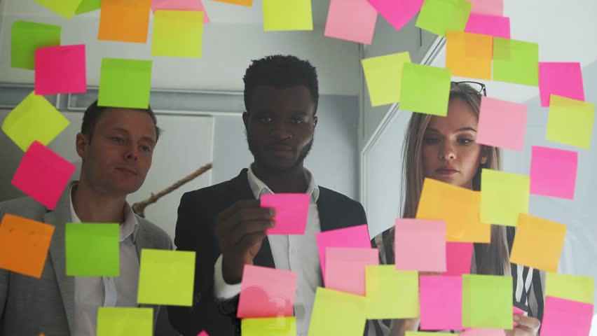Creative business team brainstorming ideas working together sharing data late at night after hours in modern glass office. | Shutterstock HD Video #1009887089