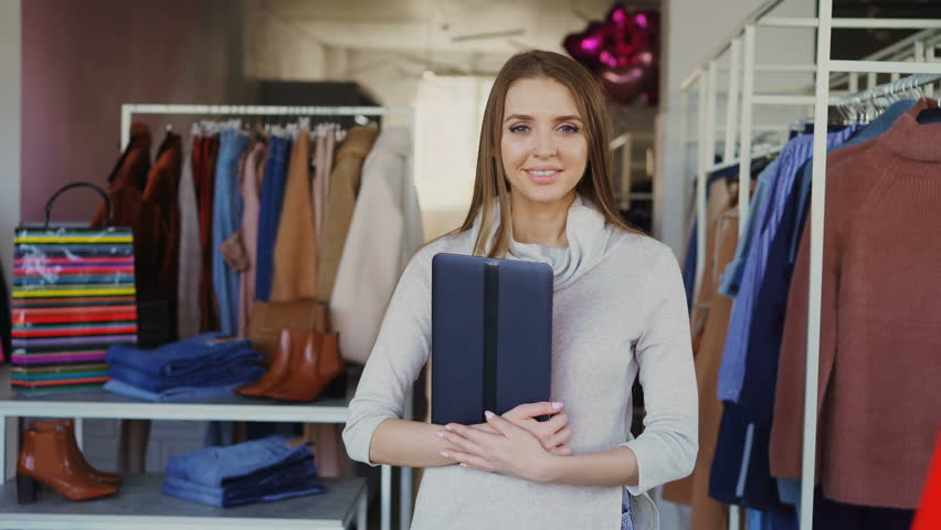 Portrait of young businesswoman standing in her clothing boutique, holding tablet, smiling and looking at camera. Spacious store with women's clothes in background.