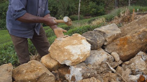 Close up of unrecognizable indian man cutting a block of granite with hammer in botanical garden. Adult human hitting stone with sledgehammer for construction flowerbed. Stonemason carving