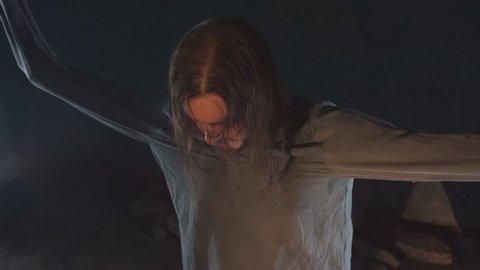 Crazy long haired caucasian man with straitjacket sleeves tied to ceiling struggling and screams in abandoned building