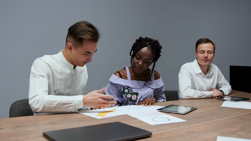 A group of creative multi-ethnic managers disassemble at the meeting of the board of directors in the conference hall the graphs of profit for the last year in the firm   Shutterstock HD Video #1009936049