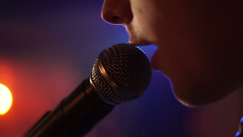 Man singing song in microphone during performance on stage on rock concert. Close up man rock star singer on music concert on colorful light background