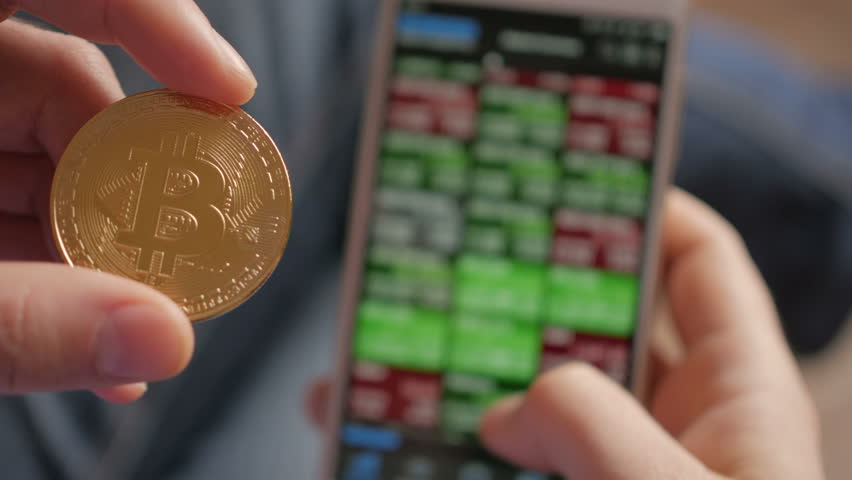 Bitcoin is a worldwide cryptocurrency and digital payment system. Businessman reading financial news. Stock market, trading online, trader working with smartphone on stockmarket trading floor. 4K UHD | Shutterstock HD Video #1009950839