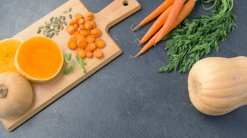 food, eating and new nordic cuisine concept - close up of hands putting bowl of pumpkin cream soup on kitchen table and adding lemon balm herb