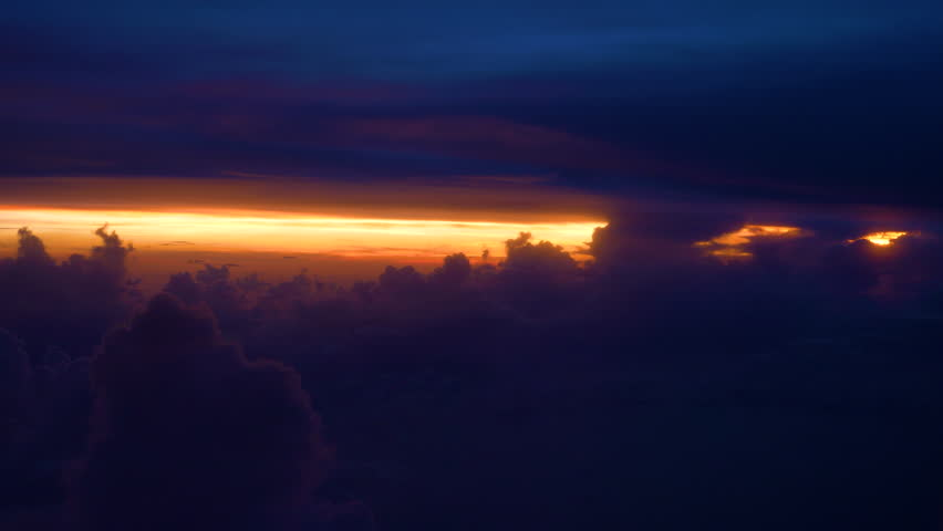 COPY SPACE, POV: Puffy clouds and purple sky cover up picturesque orange sunrise high above the Earth. Breathtaking view from an airplane window of a burnt orange sunlight peeking through dense clouds