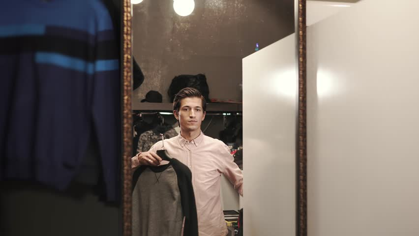 A young man looks at clothes in a mirror, places his sweaters on hangers, he wants to buy new clothes for his wardrobe in an expensive boutique   Shutterstock HD Video #1009976279