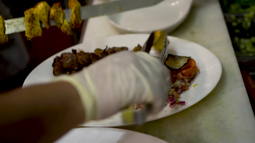 Chef slides chicken kabob off of a skewer onto a plate with beef kabob and rice with saffron.