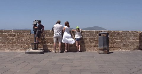 ALGHERO, SARDINIA, ITALY – JULY 2016 : Video shot of family enjoying view from city walls in central Alghero on a sunny day