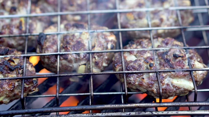 Shallow depth of field closeup of cooking kofta in grilling basket on hot grill. | Shutterstock HD Video #1009993439