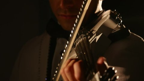 Violinist man playing the violin on a black background. Close up