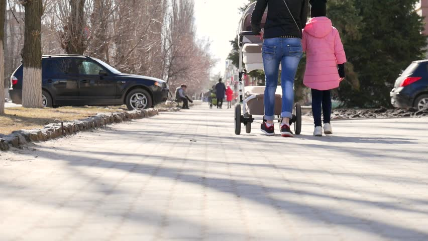 Young mother walking with daughter outdoors in a spring park pushing pram. | Shutterstock HD Video #1010009969