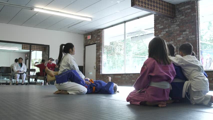 Teenage girls teaching Jiu-jitsu moves for children