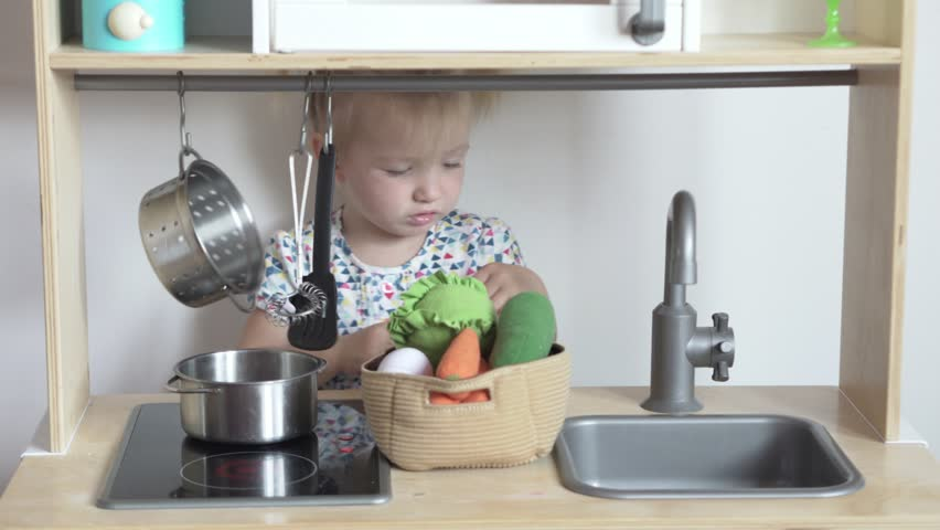 little girl is playing at a children's kitchen