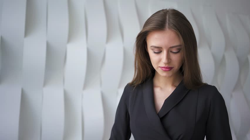 Beautiful young businesswoman wearing a suit and answering a smartphone call in a futuristic looking room. Real time medium zoom out shot. Mock up   Shutterstock HD Video #1010016569