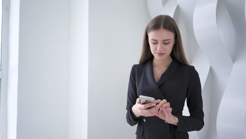 Beautiful young businesswoman wearing a suit and answering a smartphone call in a futuristic looking room. Real time medium zoom out shot. Mock up   Shutterstock HD Video #1010016719
