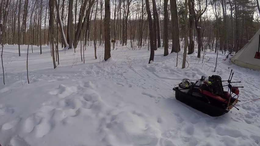 man tows camping gear away from the tent in the winter and into the woods