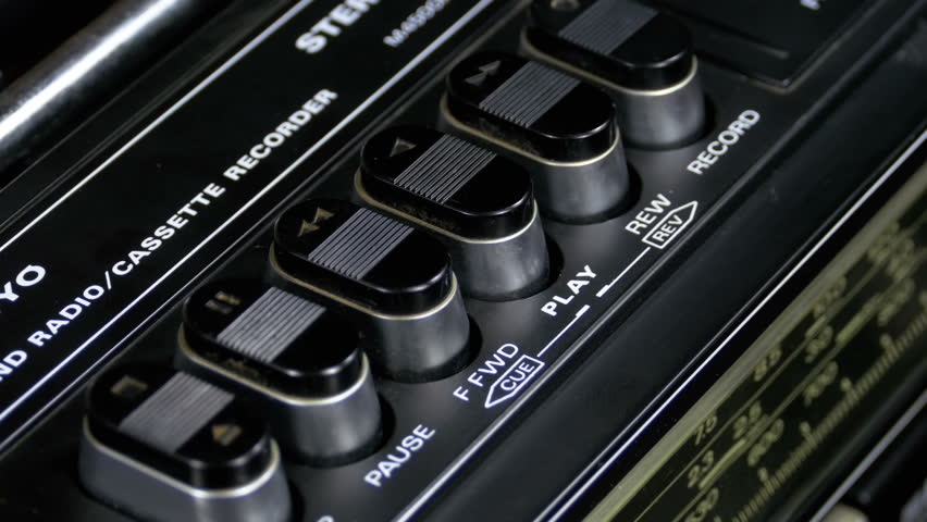 Pushing Button on a Tape Recorder, Play, Stop, Rec, ff, Rew. Close-up. Man finger presses playback control buttons on vintage audio cassette player.   Shutterstock HD Video #1010027489