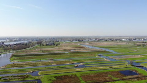 Drone footage of a green Dutch polder landscape with green wetlands and a blue sky