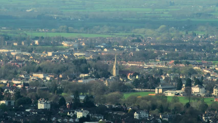 Distant town, Cheltenham, UK, with church steeple, shot with long vintage telephoto lens (part 1).