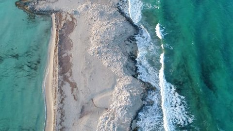 overhead aerial view looking down on waves hitting a stunning shoreline of a sandy strip of beach with water on both sides in Formentera