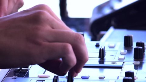 DJ hands touch buttons and sliders on sound mixing controller deck with laptops, monitors and wires, close-up. Disc jockey mix tracks, play electronic music on pro audio equipment in beach club.