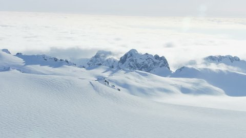 Alaska - September, 2017: Aerial view of airborne Gyrocopter flying in scenic snow covered Kenai Mountains a frozen Peninsula Wilderness area North Pacific ocean USA