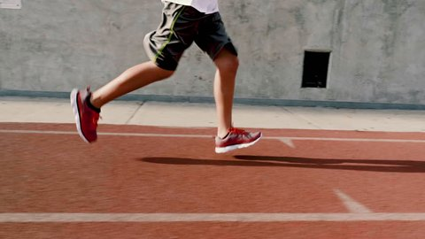 12 year old boy runs on his school's track. Close up of his feet.