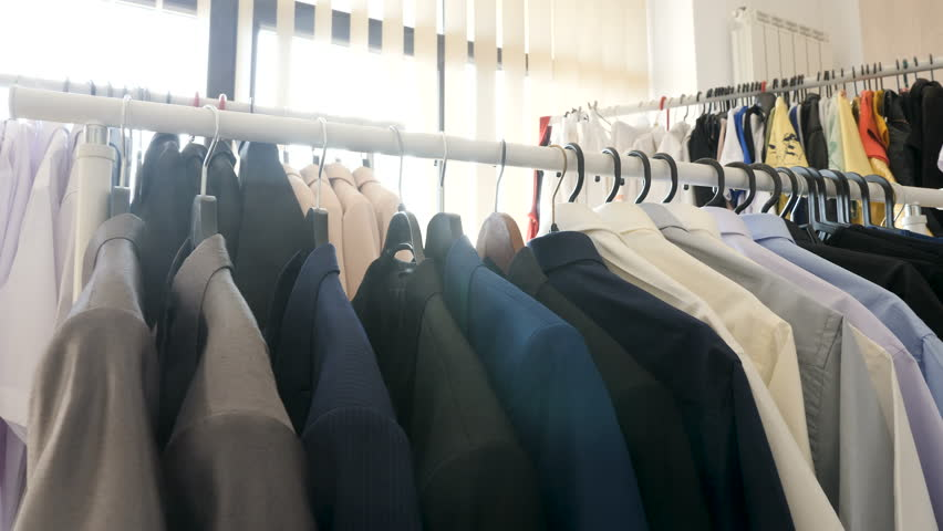 Dolly footage of hangers full with different clothes in a store next to a window. The sun rays are getting through the business suits and other clothes | Shutterstock HD Video #1010055239