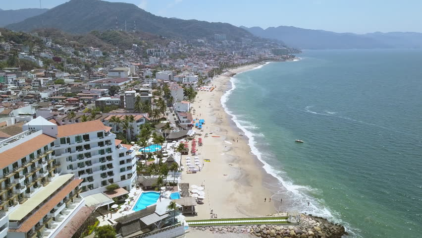 4k Aerial Drone Shot Of Puerto Vallarta's Beach, Town and Mountains. Golden Sand Waterfront Stretches Across the Coastline in this Mexico Resort Town | Shutterstock HD Video #1010056949