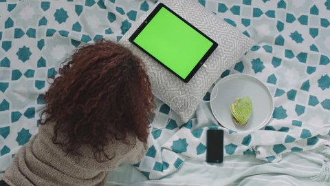 top view young woman using tablet pc watching green screen relaxing on bed at home female teenager studying chroma key