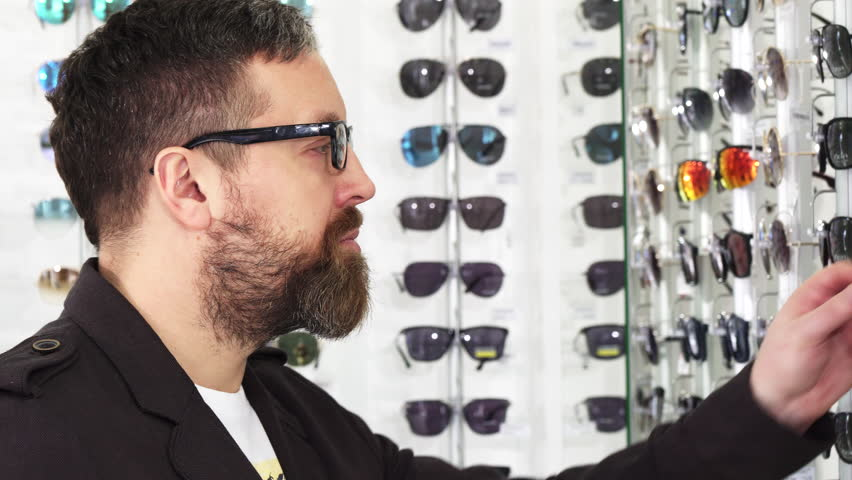 Close up of a mature man examining glasses for sale on the display   Shutterstock HD Video #1010067479