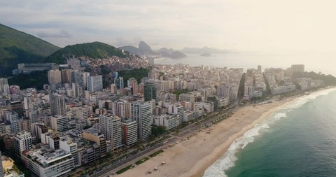 Aerial view of Rio de Janeiro flying towards Copacabana Beach with waterfront street, Brazil. Light effect applied.