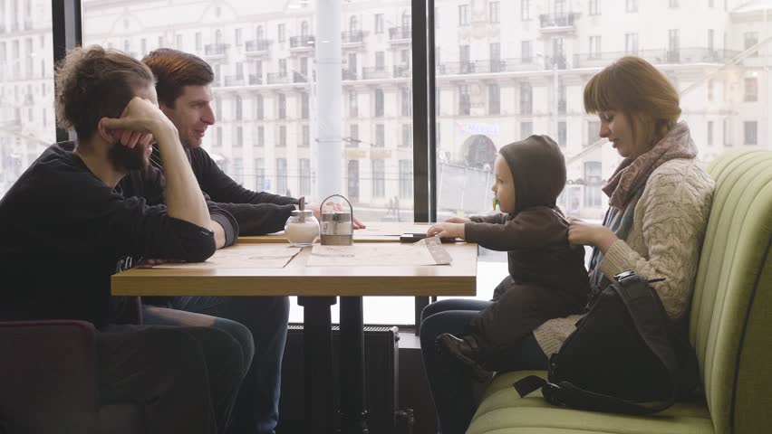 Group of Young Mixed Race People using phones in the Coffee House. Friends communicate in a cafe. | Shutterstock HD Video #1010122709