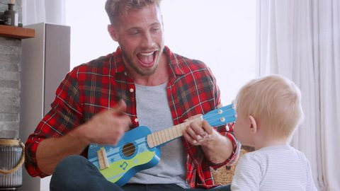 Father playing ukulele to toddler son, close up