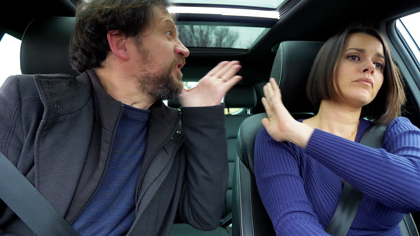 Domestic violence man showing wife fist shouting while driving car #1010139629