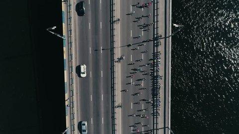 4K Aerial drone fooage. Marathon running on the bridge. Vertical dolly shot top view