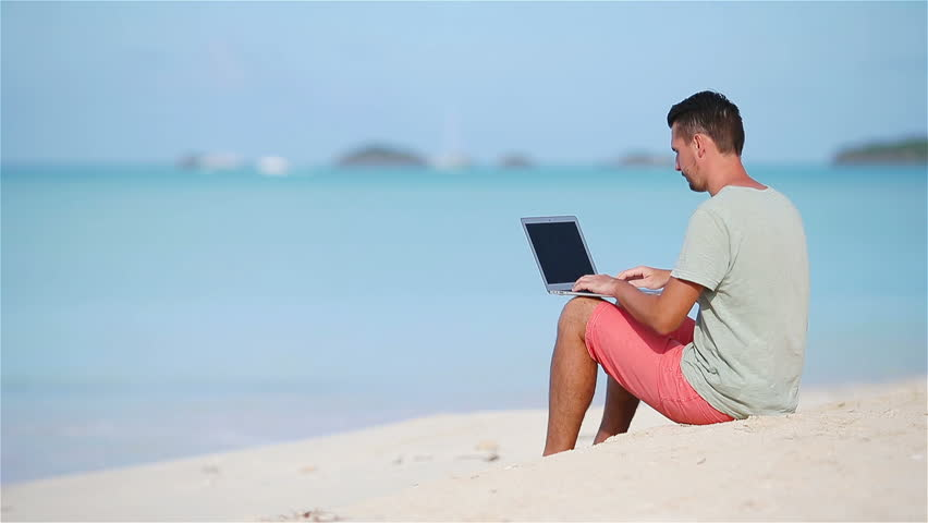 Young man with laptop on tropical beach. Man sitting with computer outdoors with beautiful view | Shutterstock HD Video #1010152109