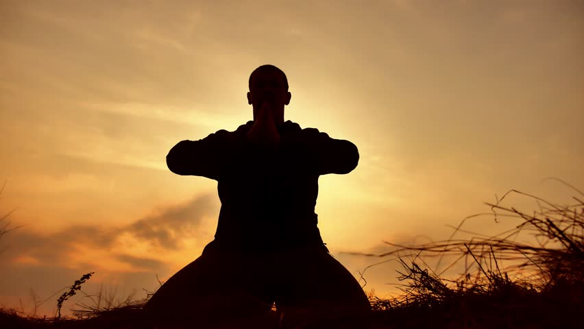 silhouette of a male monk engaged in meditation at sunset sunlight. Buddhist prays at sunset healthy way of lifestyle life nature