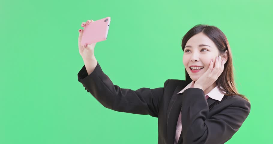 Businesswoman selfie happily on the green background | Shutterstock HD Video #1010174699