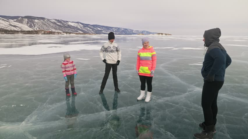 Family do sports exercises on ice in nature. Father training his family in winter. Mother daughter and son look at his training sessions. Children try to repeat them. Standard stretch before sport. | Shutterstock HD Video #1010178329